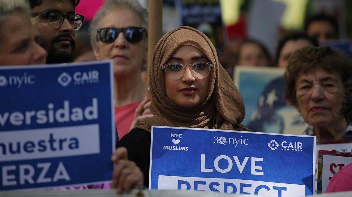 A woman holds up a poster during a rally to support Muslim rights outside City hall on June 10, 2017, in New York. (AFP)