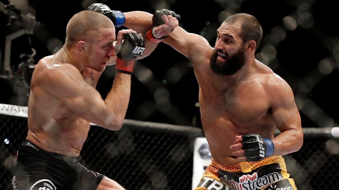 In this Nov. 16, 2013 file photo, Johny Hendricks, right, exchanges punches with Georges St. Pierre during a UFC 167 mixed martial arts championship welterweight bout in Las Vegas. (AP)