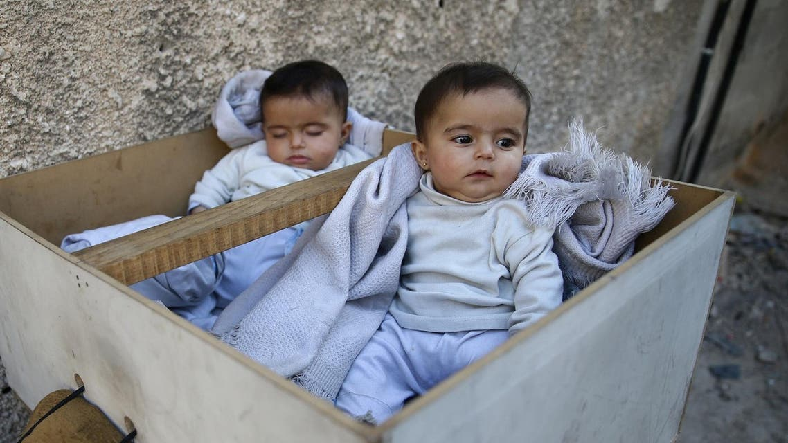 Five-month-old twins Farah and Marah wait for their parents to receive milk distributions from a medical center in the Hamoria area, in the eastern Damascus suburb of Ghouta, Syria, October 25, 2017. (Reuters)