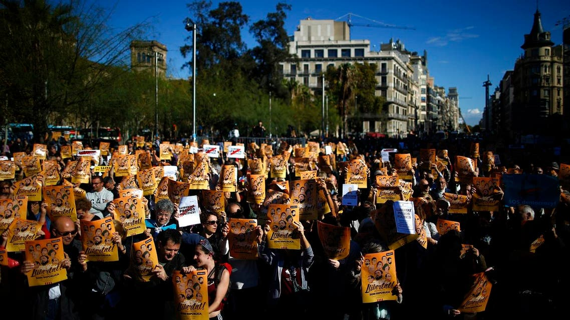 """Demonstrators holding banners that read in Catalan: """"Freedom for the Political Prisoners"""", gather during a protest against the decision of a judge to jail ex-members of the Catalan government. (AP)"""