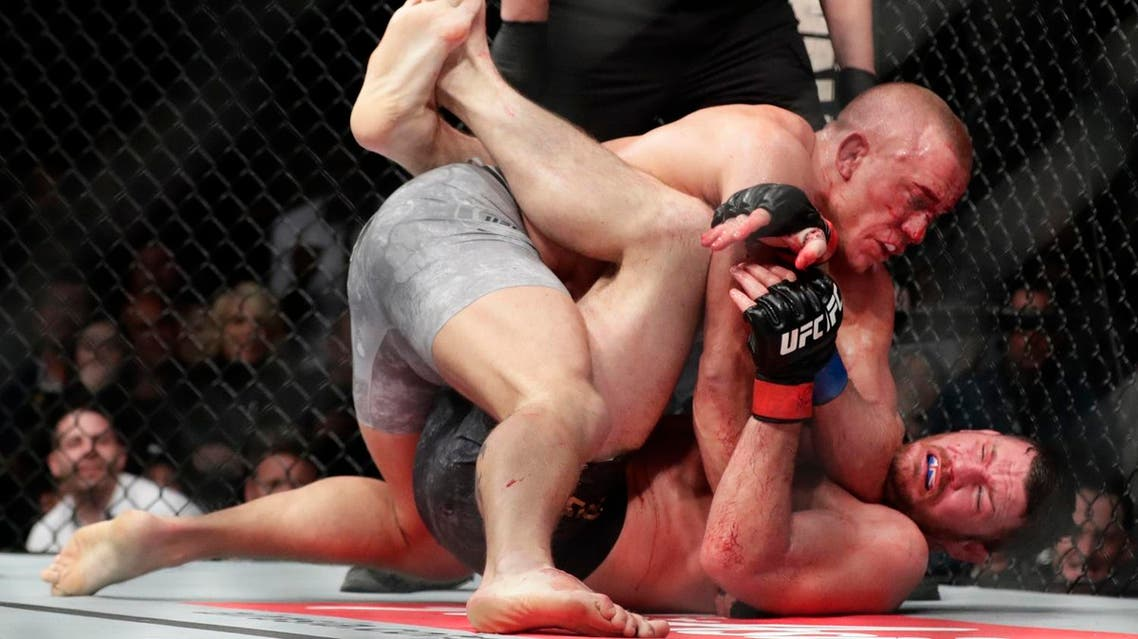 Georges St-Pierre, above, of Canada, fights England's Michael Bisping during a middleweight title mixed martial arts bout at UFC 217 Sunday, Nov. 5, 2017, in New York. St-Pierre won the fight. (AP)
