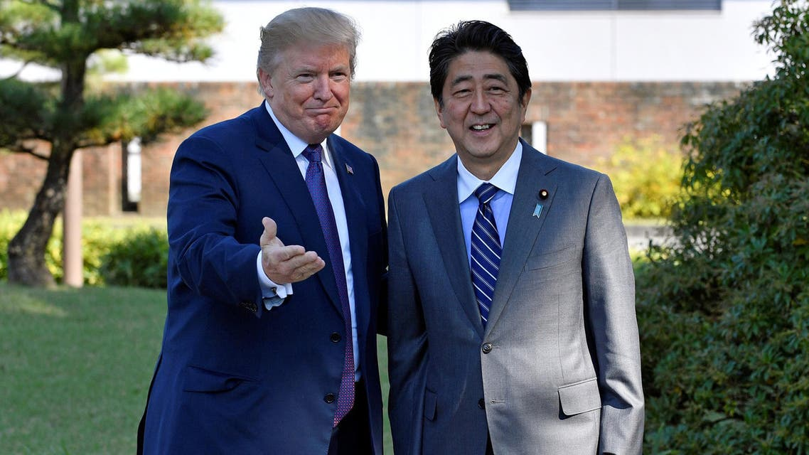 US President Donald Trump (L) gestures with Japanese Prime Minister Shinzo Abe upon his arrival at the Kasumigaseki Country Club in Kawagoe, near Tokyo, Japan, 05 November 2017. REUTERS/Frank Robichon/Pool