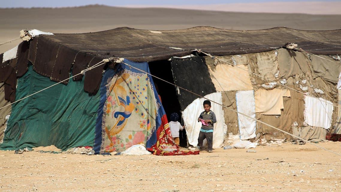 Iraqi children, displaced from the city of al-Qaim, stand outside a tent near al-Qaim, in western Anbar province, on the Syrian border on November 2, 2017.  AHMAD AL-RUBAYE / AFP