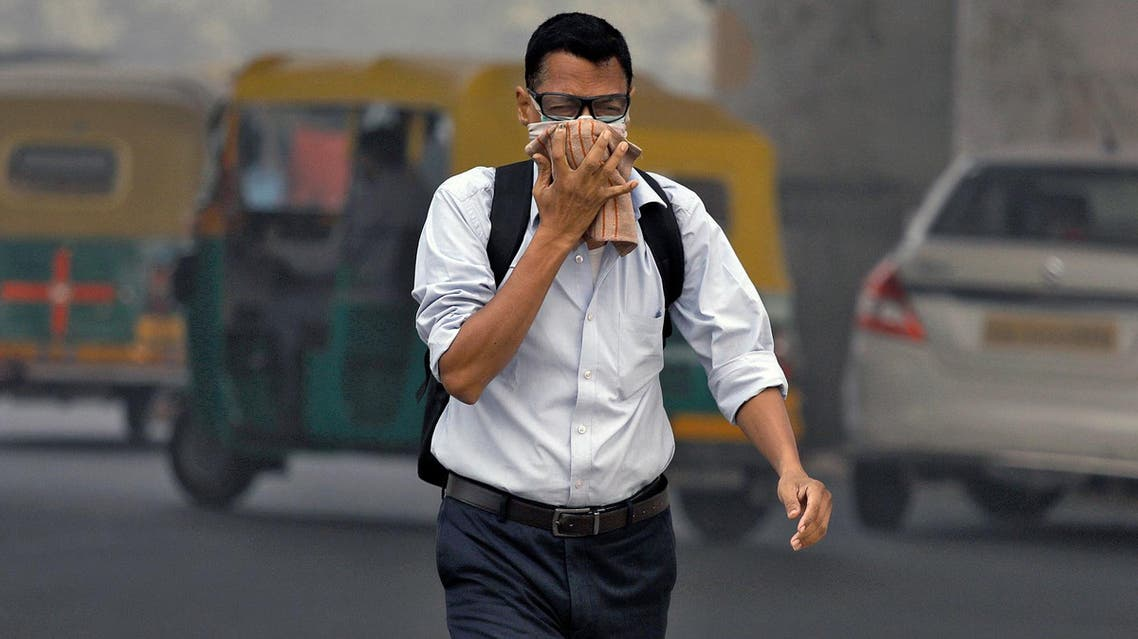 A man covers his face as he walks to work, in Delhi, on November 7, 2017. (Reuters)