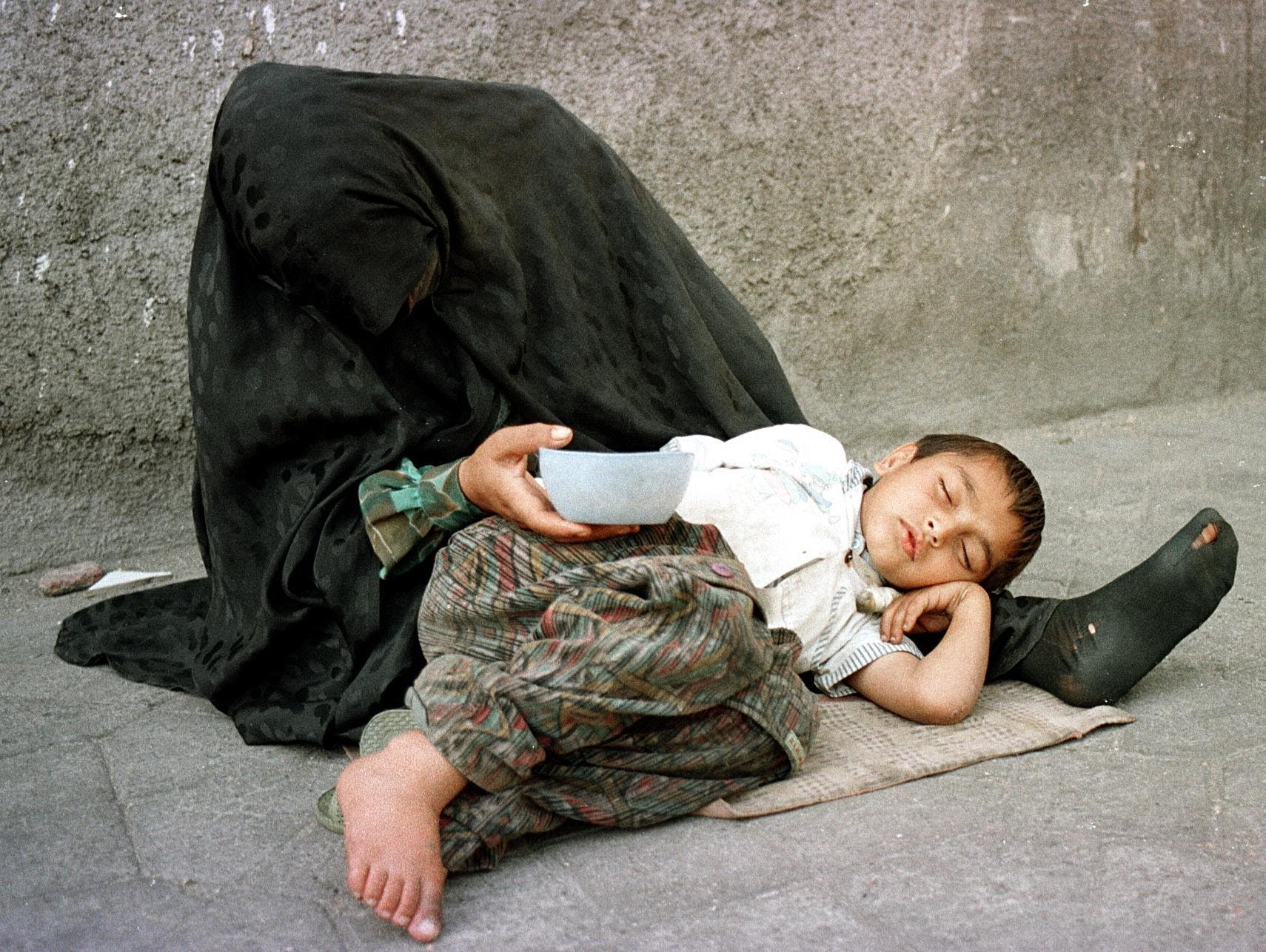 A homeless woman and her child beg for money 22 May 1999 in Tehran. (AFP)