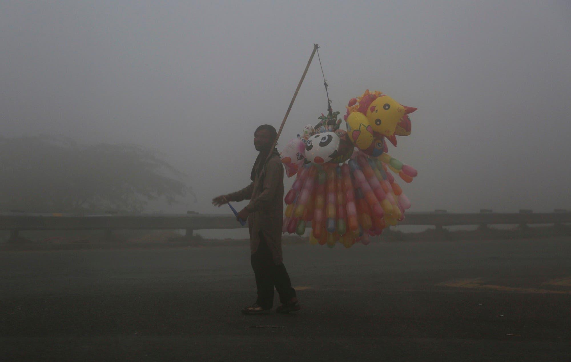 A Pakistani vendor sells balloons while fog envelopes the area in Lahore, Pakistan, on Nov. 8, 2017. (AP)