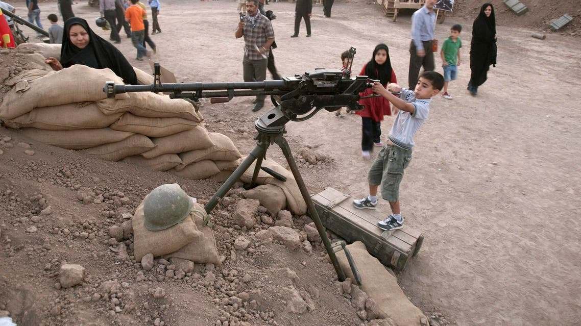 An Iranian boy plays with a weapon at a war exhibition in Tehran on September 26, 2011. (Reuters)