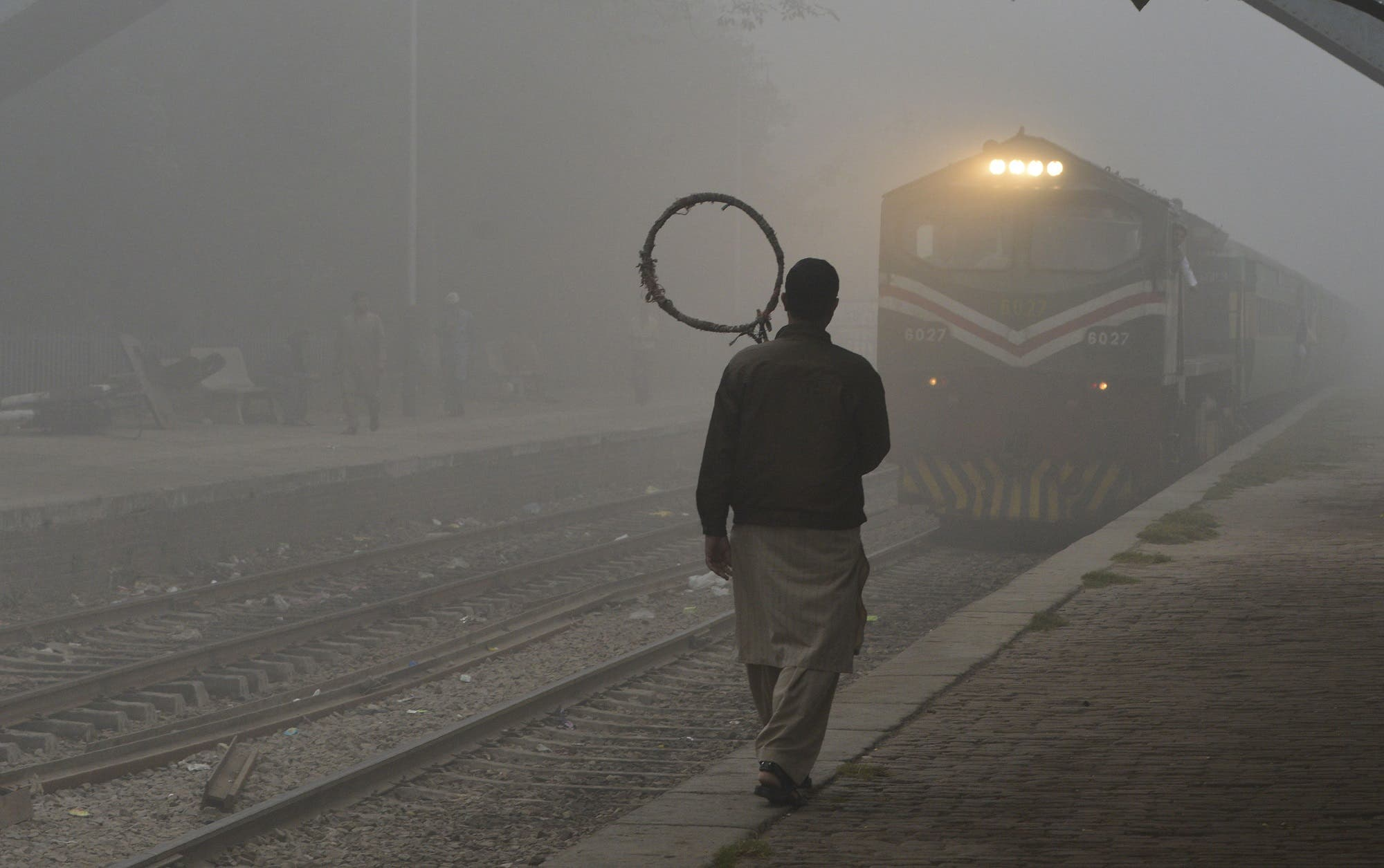 A Pakistani railway worker walks on the platform while a train arrives at a station in heavy smog in Lahore on November 6, 2017. (AFP)