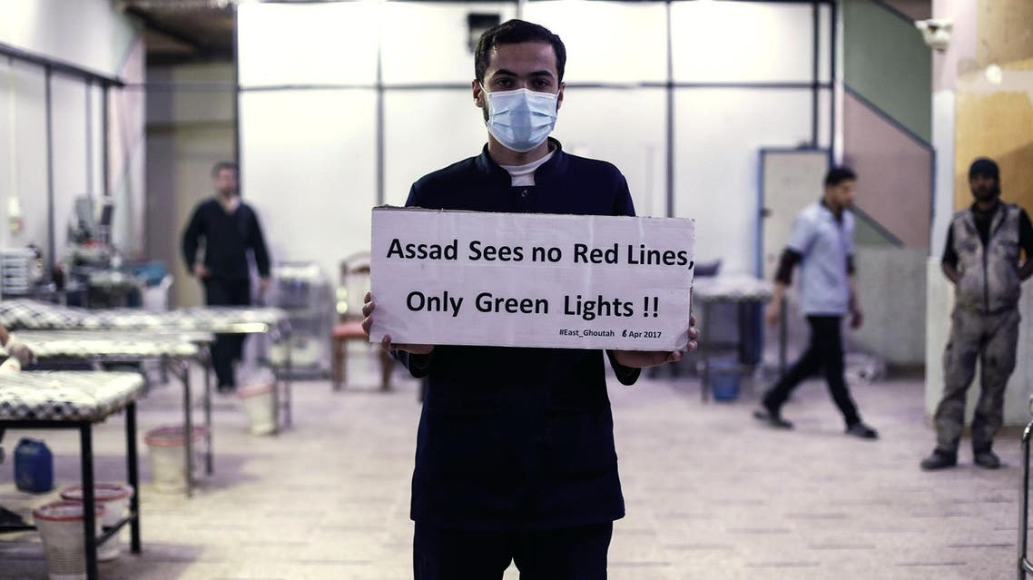 A medical staff at a hospital holds a placard condemning a suspected chemical weapons attack on Khan Sheikhun on the outskirts of Damascus on April 6, 2017. (AFP)