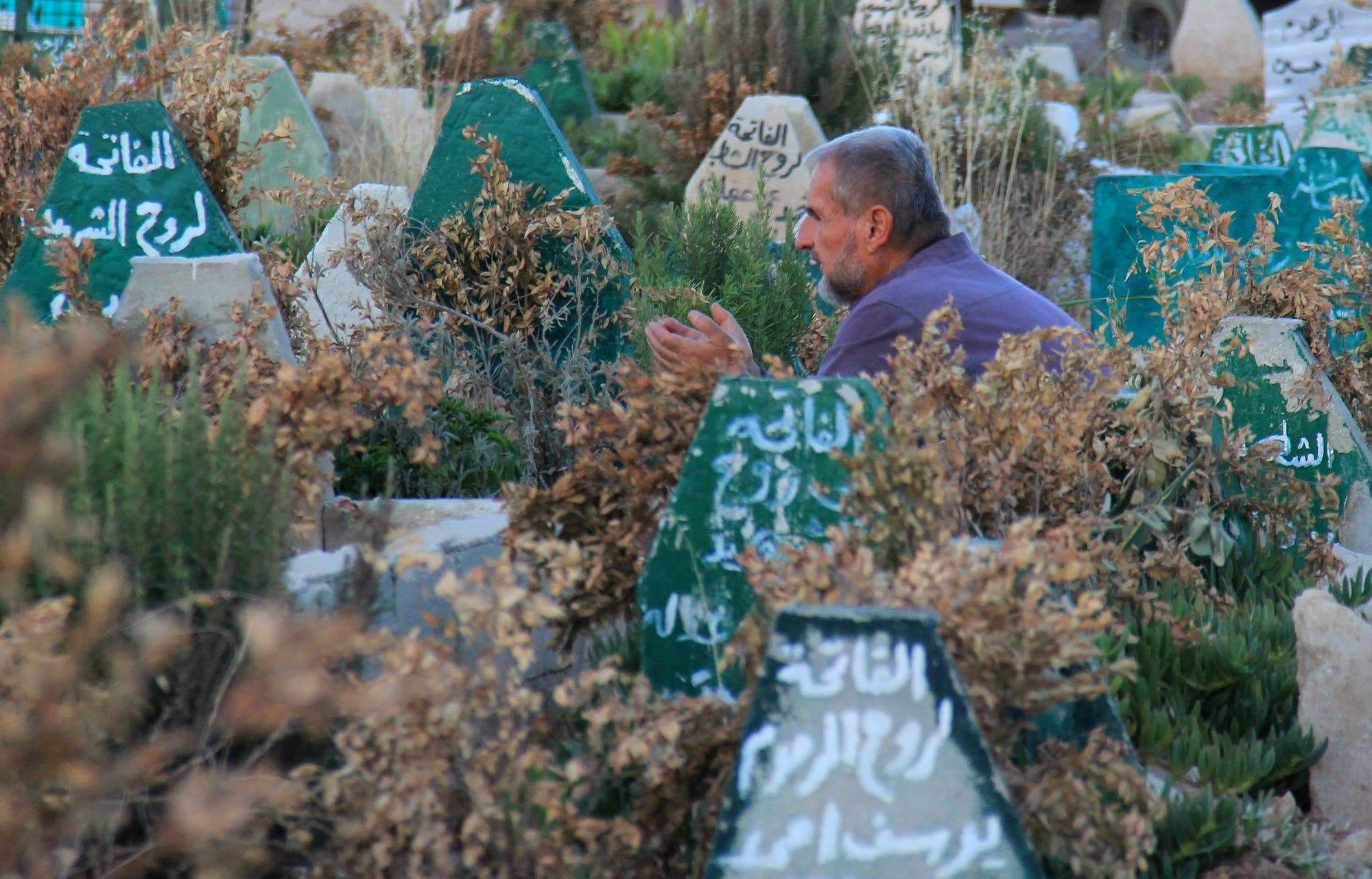 A Syrian man prays on July 12, 2017 at a cemetery in Khan Sheikhun. (AFP)