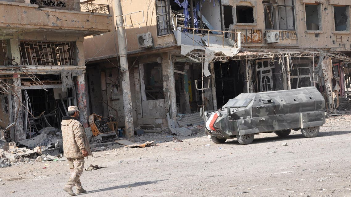 A general view shows a Syrian pro-government forces member walking past damaged buildings in the eastern city of Deir Ezzor on November 4, 2017. Syrian and allied forces converged on holdout Islamic State group fighters in the Syrian border town of Albu Kamal, the jihadists' very last urban bastion following a string of losses. On November 3, Russian-backed Syrian regime forces took full control of Deir Ezzor, which was the last city where IS still had a presence after being expelled from Hawija and Raqa last month  STRINGER / AFP