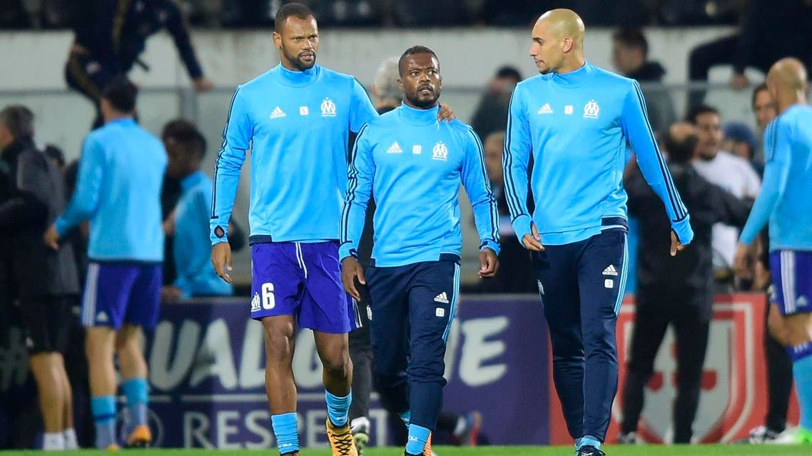 Marseille's French defender Patrice Evra (C) escorted off the pitch by teammates Portuguese defender Rolando and Brazilian defender Doria after an argument with supporters. (AFP)
