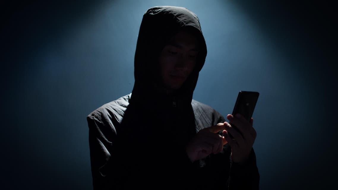 Hacker holding phone - Stock image...