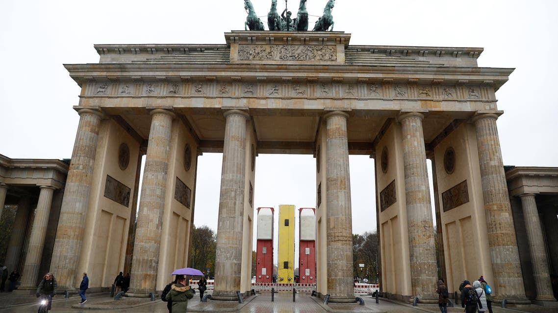 """An installation """"Monument"""" by German-Syrian artist Manaf Halbouni stands in front the Brandenburg Gate in Berlin, Germany, November 10, 2017. The installation, previously displayed in Dresden, displays three upended buses to mimic a defensive barricade erected in Aleppo, in Syria, to protect people from sniper fire. REUTERS/Fabrizio Bensch"""