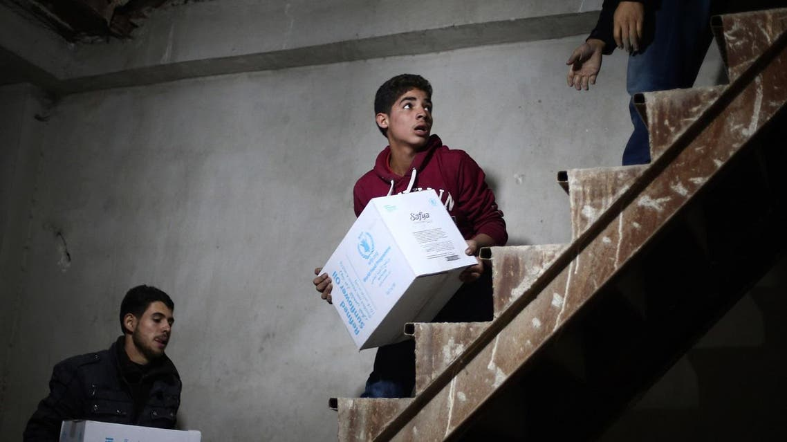 """Syrian youths unload humanitarian aid parcels from a Syrian Red Crescent truck in the besieged rebel-held Eastern Ghouta region outside Damascus on October 30, 2017. The joint UN-Syrian Arab Red Crescent convoy included 49 trucks carrying """"eight thousand food parcels and a similar number of bags of flour, medicine, medical supplies, and other nutritional materials,"""" Red Crescent spokeswoman Mona Kurdi said. (AFP)"""