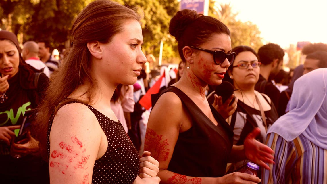 Women, with red paint on their bodies to symbolize blood, protest against sexual harassment in front of the opera house in Cairo June 14, 2014. (Reuters)