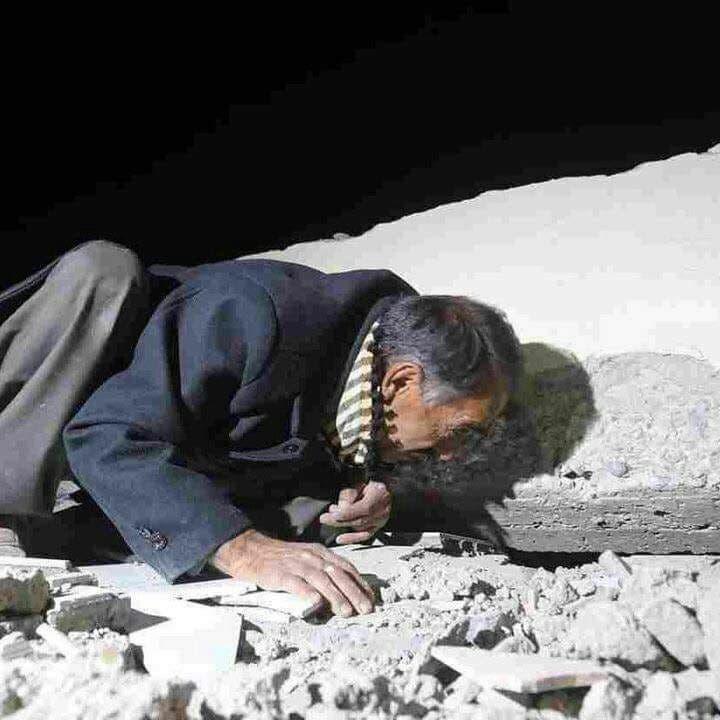 تصویری از یک شهروند کرد ایرانی که در جستجوی افراد زیر آوار
