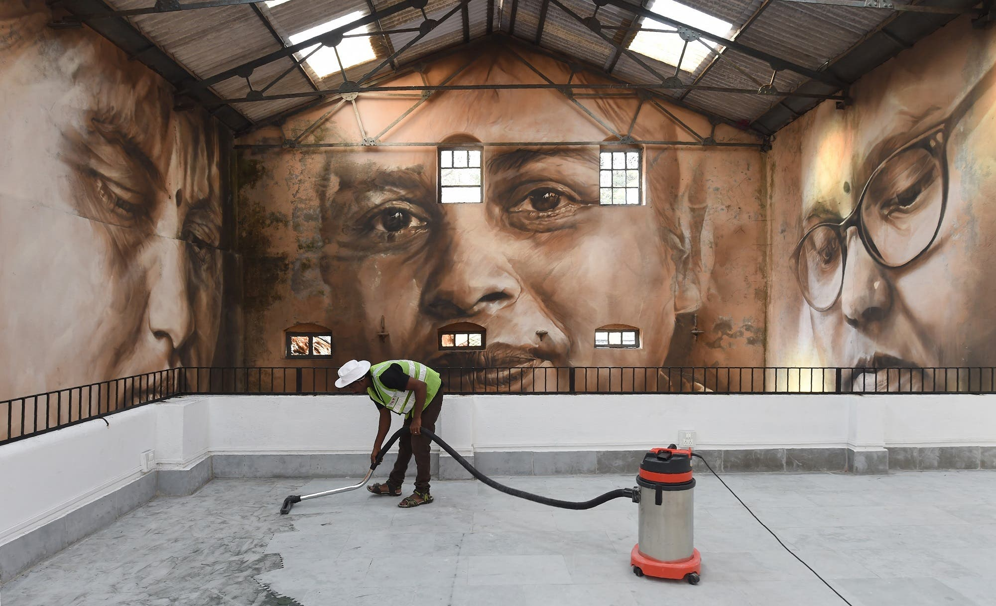 A worker cleaning the viewing area in front of a photo mural of the St+art Festival at Sassoon Dock. (AFP)