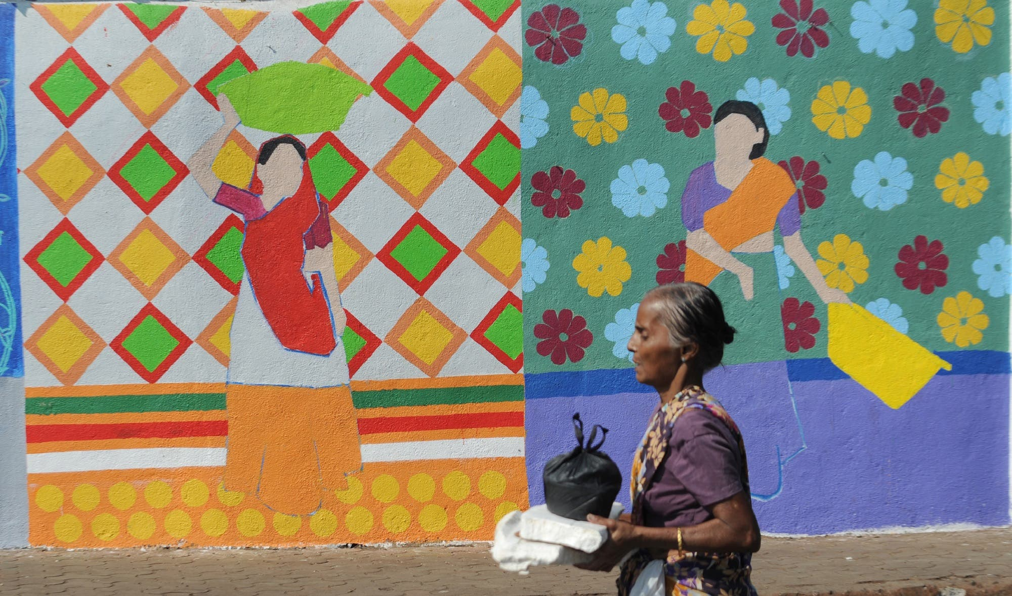This November 9, 2017 photo shows a fisherwoman walking past a wall painting of the St+art Festival at Sassoon Dock, one of the oldest fishing docks in Mumbai. (AFP)
