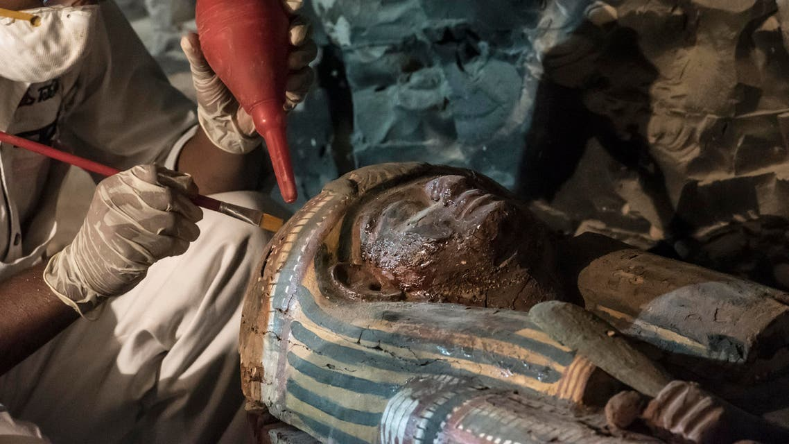 "A picture taken on September 9, 2017 shows Egyptian archaeologist restoring a wooden sacrophagus at a newly-uncovered ancient tomb for a goldsmith dedicated to the ancient Egyptian god Amun, in the Draa Abul Naga necropolis on the west bank of the ancient city of Luxor, which boasts ancient Egyptian temples and burial grounds. The finds at the tomb of ""Amun's Goldsmith, Amenemhat"", which dates back to the New Kingdom (16th to 11th centuries BC), AFP"