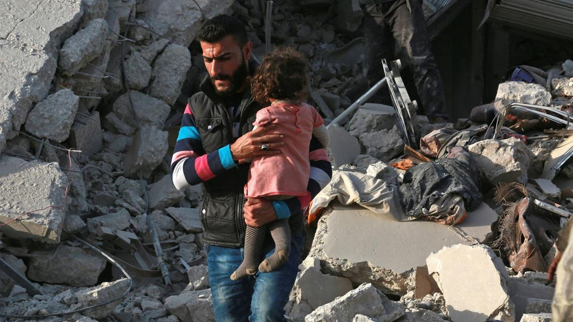 "A Syrian man carries a child following a reported airstrike on the rebel-held town of Atareb in Syria's northern Aleppo province on November 13, 2017. At least 21 civilians, including five children, were killed on Monday in air strikes on Syria's northern Aleppo province, despite a ""de-escalation zone"" in place there, the Britain-based Syrian Observatory for Human Rights said . (AFP)"