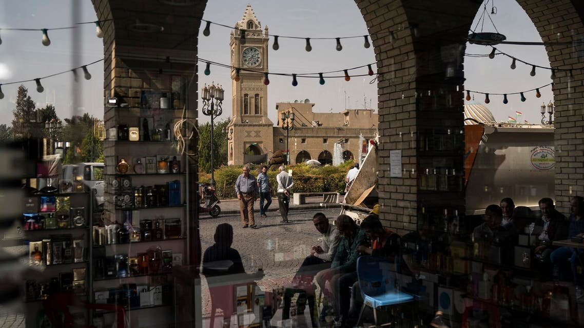 People are reflected in the window of a closed shop in central Irbil, Iraq, Wednesday, Oct. 25, 2017. (AP)