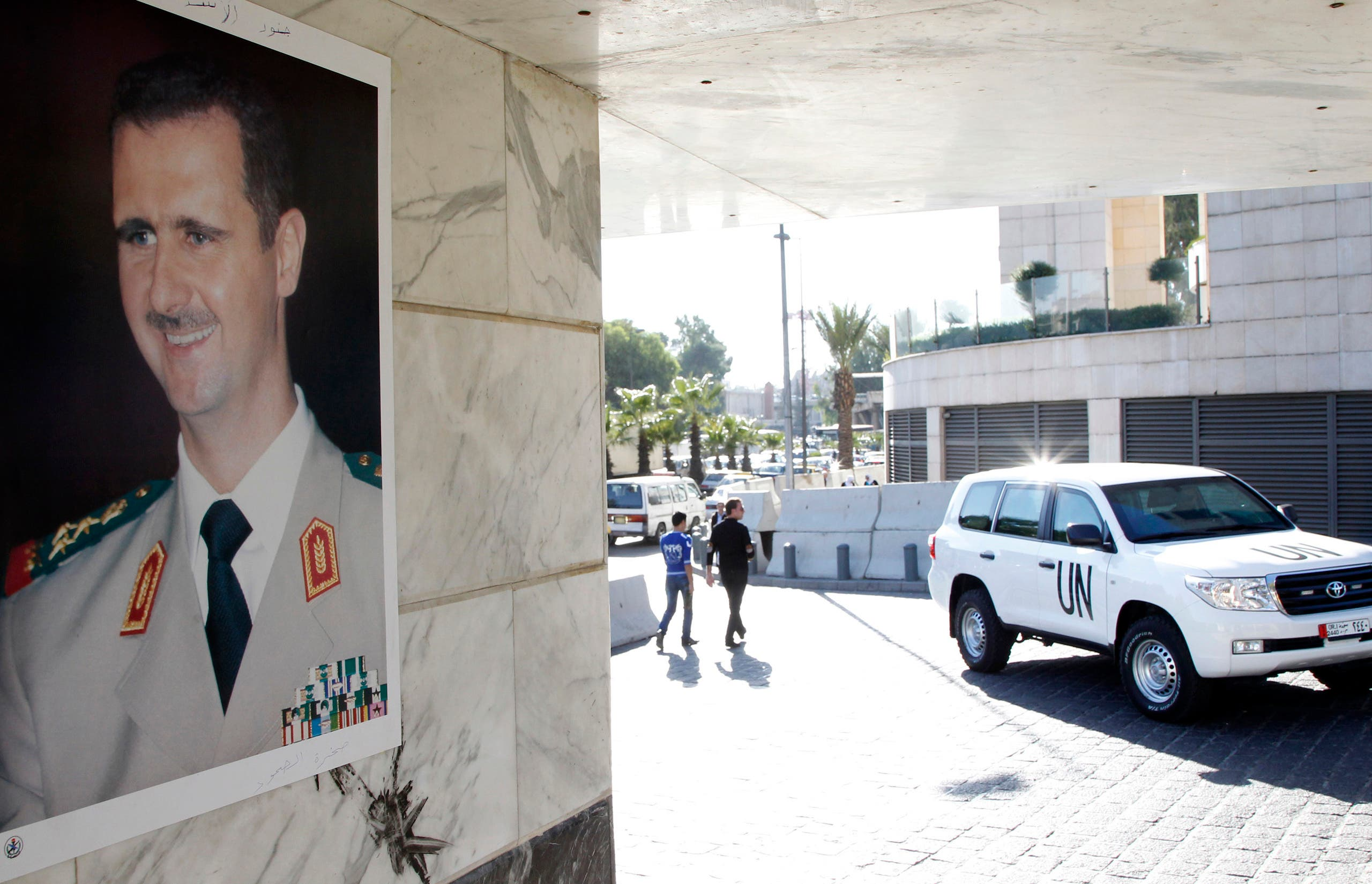 A UN vehicle is seen near a photo of Bashar al-Assad at the entrance of a hotel where a team of experts stayed in Damascus October 8, 2013. (Reuters)