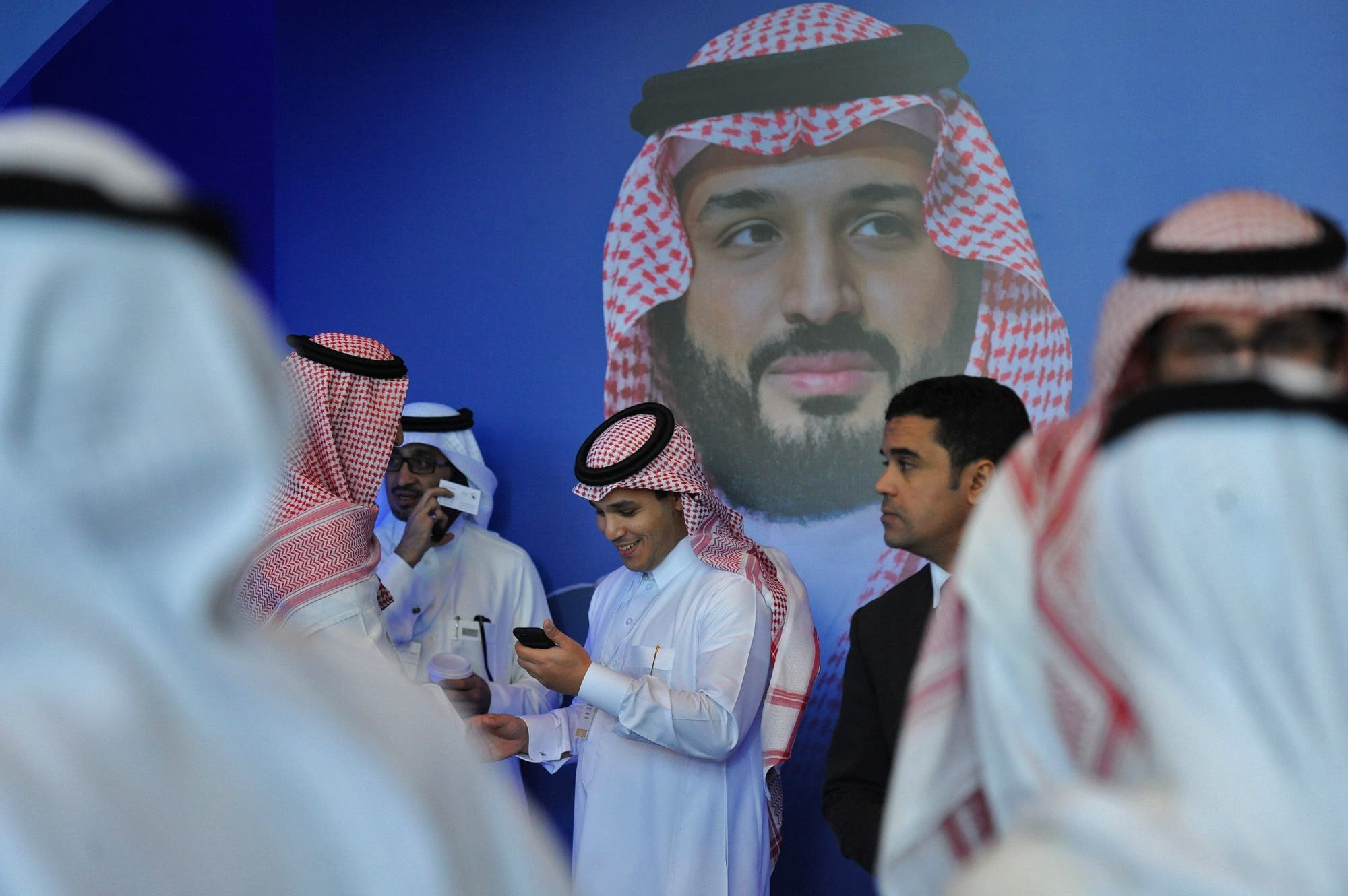 Saudi men chat in front of a poster of Saudi Crown Prince Mohammed bin Salman during the MiSK Global Forum in Riyadh, on November 15, 2017. (AFP)