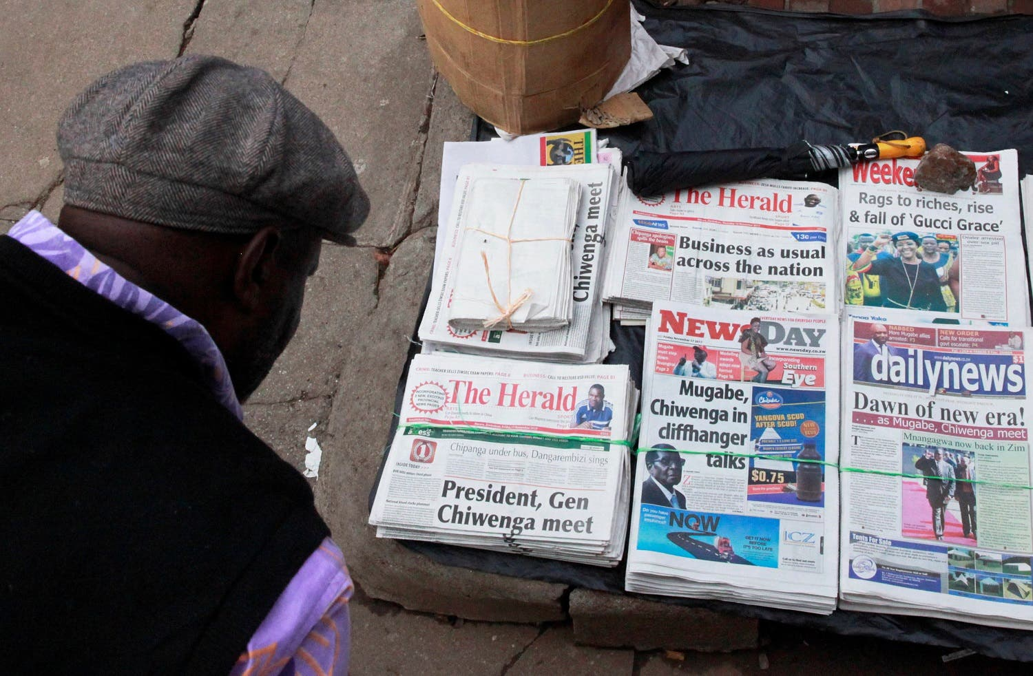 A man reads the headlines of newspapers for sale on a street in Harare, Zimbabwe, on November 17, 2017. (Reuters)