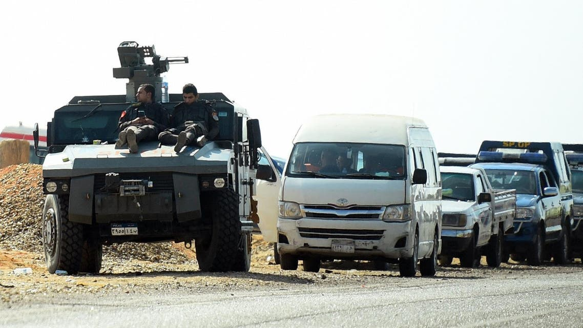 Egyptian security forces' vehicles and armored personnel carriers (APCs) parked on the desert road near the site of an attack that left at least a dozen policemen killed in an ambush by militant fighters. (AFP)