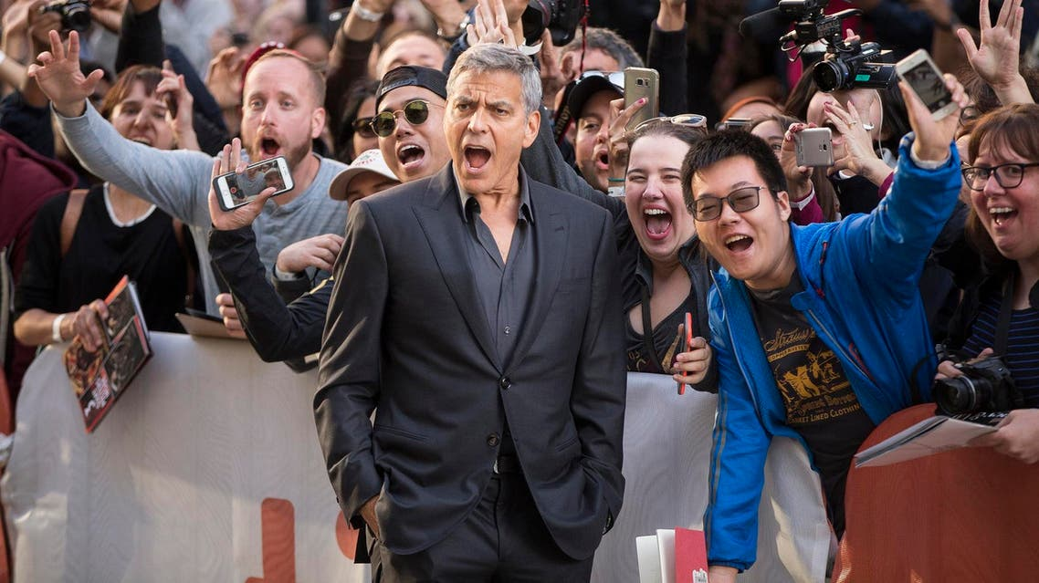 """Clooney poses with fans at the premiere of """"Suburbicon"""" at the Toronto International Film Festival on September 9, 2017. (AFP)"""