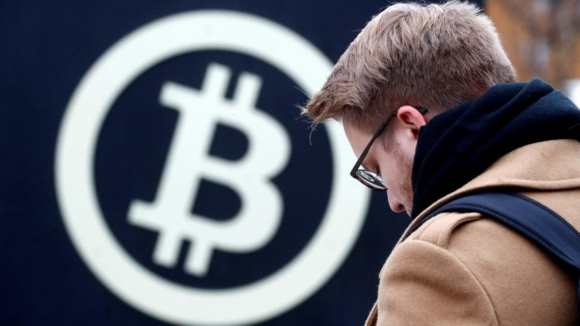 A man stands next to the bitcoin sign during Riga Comm 2017, a business technology and innovation fair in Riga, Latvia November 9, 2017. (Reuters)