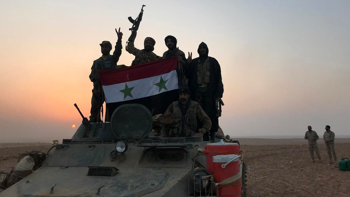 Syrian forces gestures as they carry the national flag in the village of Suway'iah, near the Syrian border town of Albu Kamal, on November 9, 2017. (AFP)