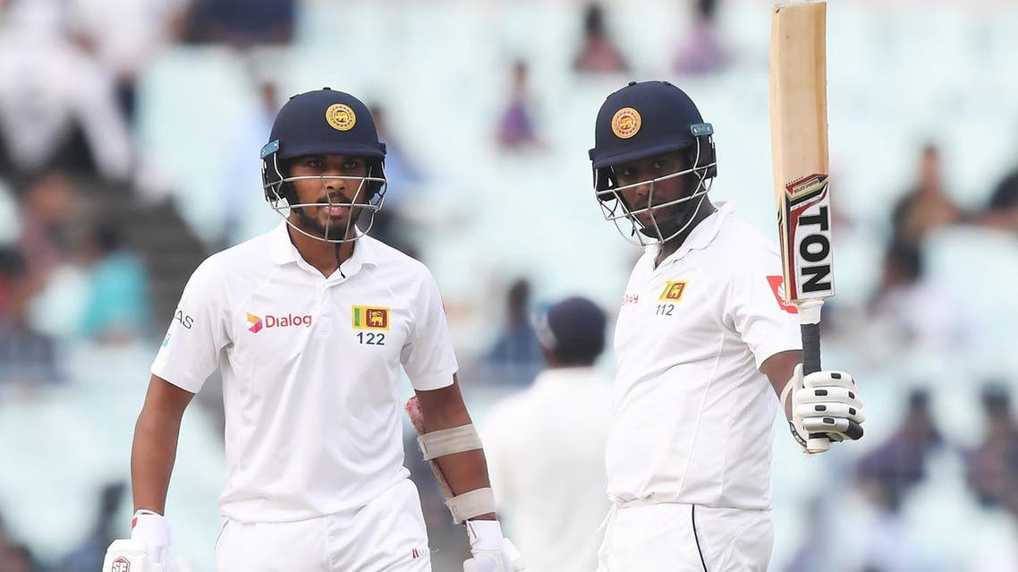 Sri Lanka's Angelo Mathews celebrates after scoring a half-century (50 runs) as captain Dinesh Chandimal looks on during the third day of the first Test between India and Sri Lanka at the Eden Gardens cricket stadium in Kolkata on November 18, 2017. (AFP)
