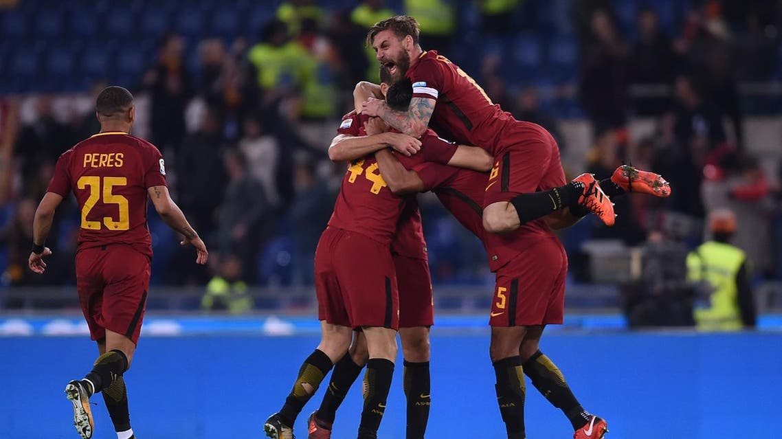 Roma's Italian midfielder Daniele De Rossi (top) celebrates with teammates at the end of the Italian Serie A football match AS Roma vs Lazio on November 18, 2017 at the Olympic stadium in Rome. AS Roma won 2-1.  Filippo MONTEFORTE / AFP