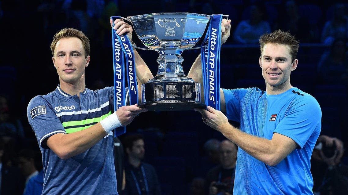 Finland's Henri Kontinen and Australia's John Peers hold the winner's trophy after winning their men's doubles final match against Brazil's Marcelo Melo and Poland's Lukasz Kubot on day eight of the ATP World Tour Finals tennis tournament at the O2 Arena in London on November 19, 2017. Kontinen and Peers won 6-4, 6-2. AFP