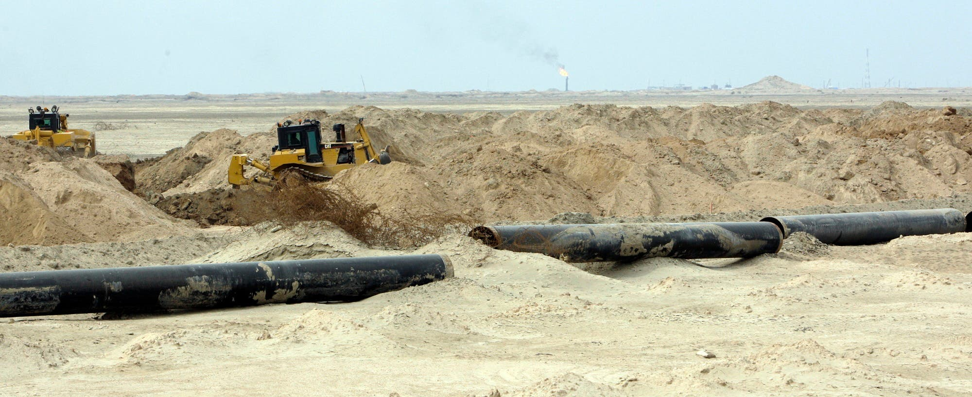 Pipes are put in place as the land is cleared from ordnance and mines laid down during the Iraq-Iran war 1980-1988, in the massive Majnoon oil field, some 40 kms from the eastern border with Iran, on February 7, 2012, in southeastern Iraq. (AFP)
