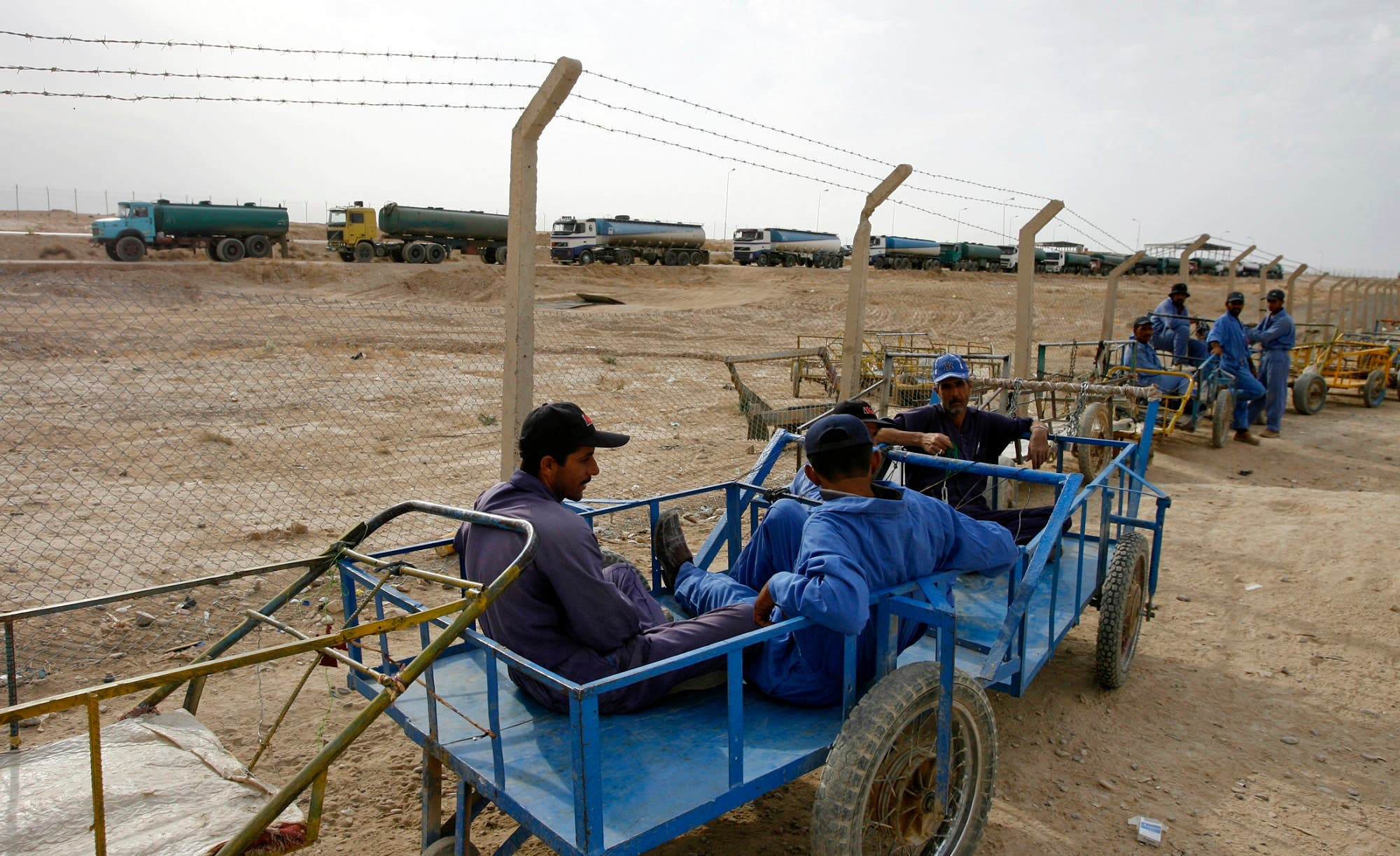 Iraqi porters sit on their carts as they wait for customers overlooking Iran bound oil tankers at the new Zurbatia checkpoint, 120 km southeast of Baghdad November 17, 2007. (Reuters)