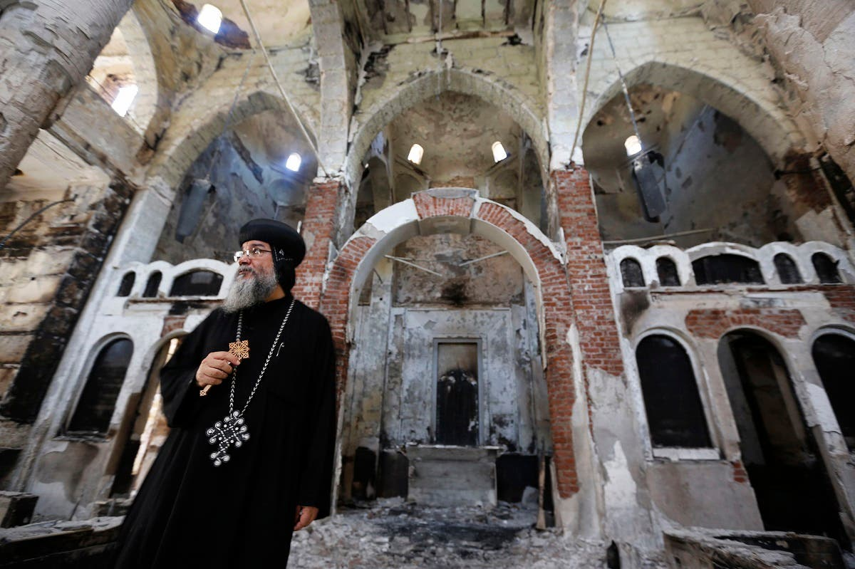 Bishop-General Macarius, a Coptic Orthodox leader, walks around the burnt and damaged Evangelical Church in Minya governorate, about 245 km (152 miles) south of Cairo, August 26, 2013. (Reuters)