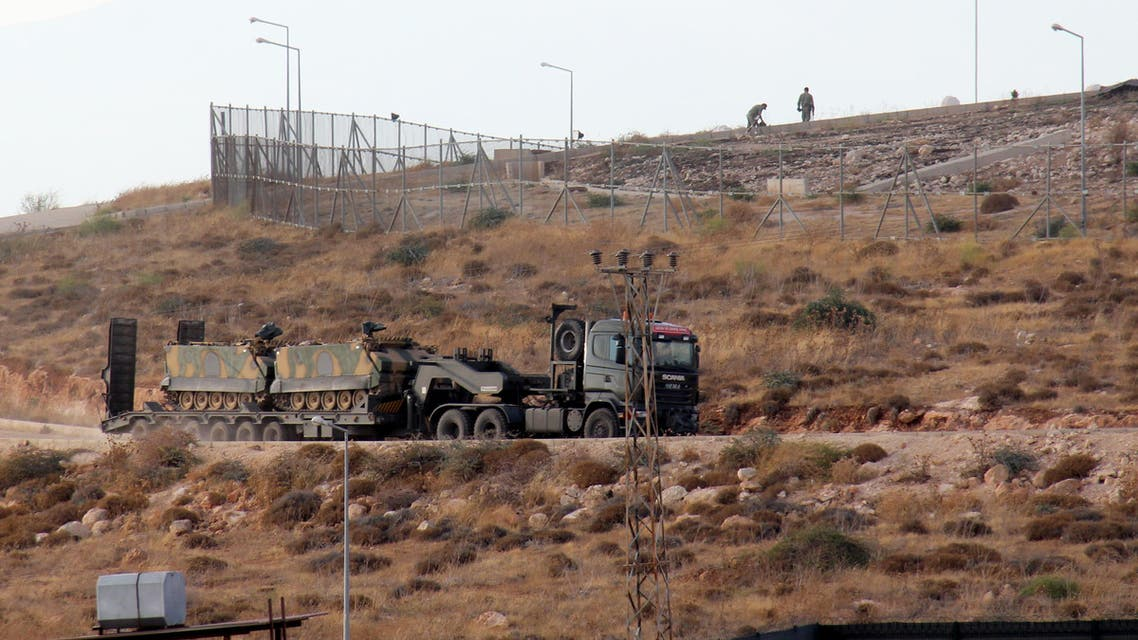 A picture taken on October 11, 2017, from the Syrian village of Atme in the northwestern province of Idlib shows Turkish military vehicles driving around a military base on the Turkish side of the border with Syria. Turkey-backed Syrian rebels are preparing for an operation to oust jihadists from the northwestern province of Idlib. Early this week, Turkey's army said it had launched a reconnaissance mission in Idlib days after President Recep Tayyip Erdogan announced an incursion to oust Al-Qaeda's former Syrian affiliate from the area.  Omar haj kadour / AFP