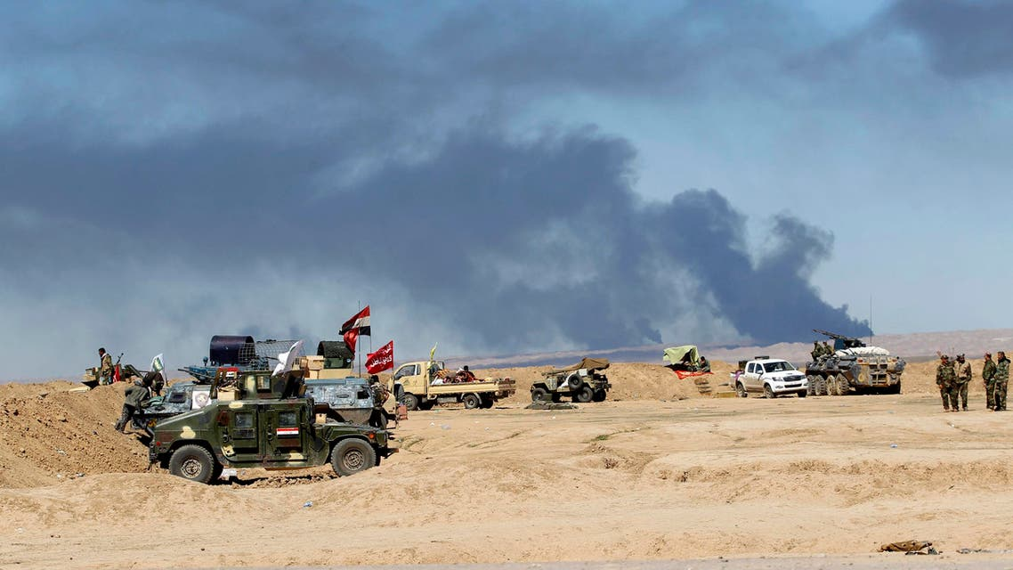 Smoke rises from the Ajil oil field as Shi'ite fighters stand near their vehicles in Al Hadidiya, where they were preparing to launch an offensive on March 6, 2015. (Reuters)