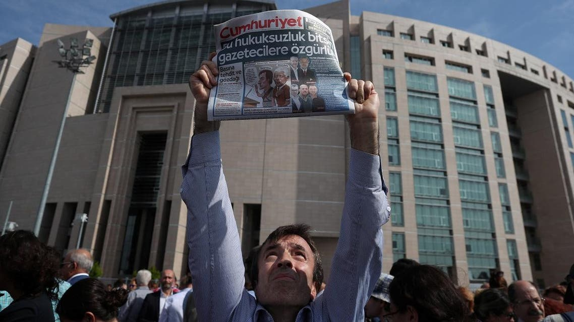 A press freedom activist holds a copy of the opposition newspaper Cumhuriyet during a demonstration in solidarity with the jailed members of the opposition newspaper Cumhuriyet outside a courthouse, in Istanbul. (Reuters)