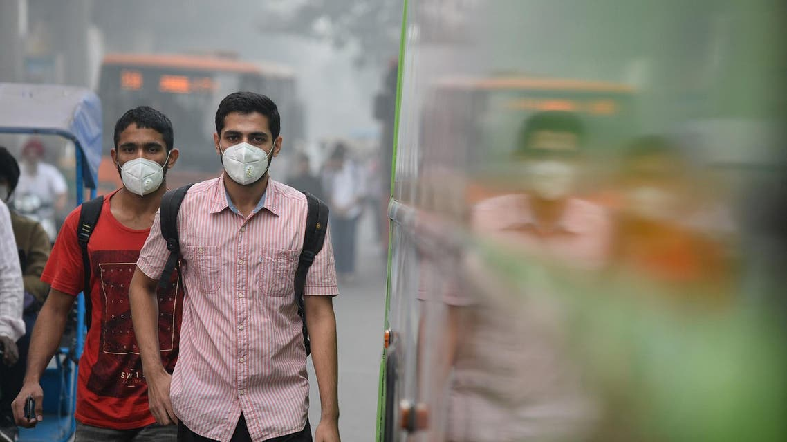 Indian commuters wear masks as they walk along a road amid heavy smog in New Delhi on November 9, 2017. (AFP)