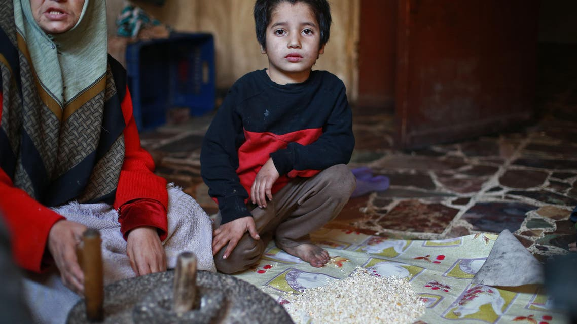 A seven -year-old boy poses for a photo as women from the family of Umm Saeed grind corn using a traditional method prior to preparing a plate of corn and cabbage, on November 6, 2017 in Saqba, in the besieged rebel-held Eastern Ghouta area near Damascus, where residents and relief groups have warned a humanitarian crisis is escalating. Eastern Ghouta was once a prime agricultural region famed for its orchards, but the rebel stronghold has been under a tight government siege since 2013, causing shortages of food and medicine.  ABDULMONAM EASSA / AFP