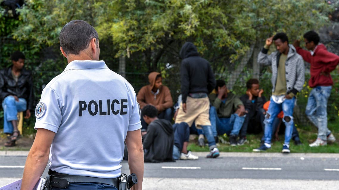 A police officer watches migrants who wait on a road, near the port of Calais, northern France, on August 16, 2017. The Lille court demanded that the migrants who decide to seek asylum in France be offered a place in a reception centre wherever there is space available. Between 450 and 700 migrants are thought to be sleeping rough in the region. PHILIPPE HUGUEN / AFP