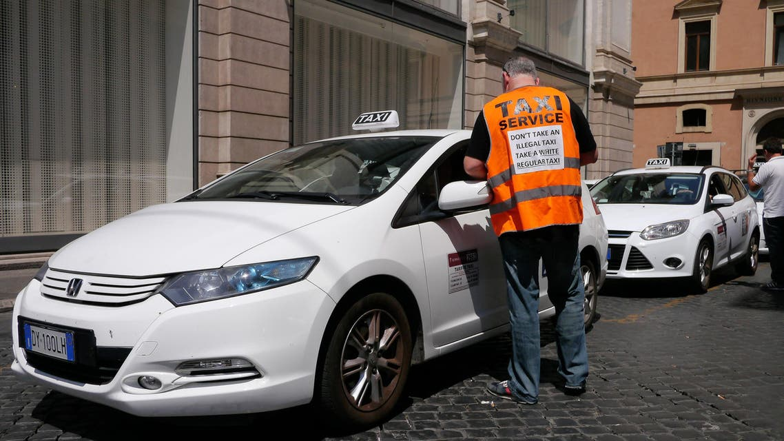 """Italian taxi drivers hold a placard reading """"Don't take an illegal taxi, take a white regular taxi"""" during a protest against the growing number of minicabs and cars, known in Italy as """"Car rental with driver"""" (NCC), on June 11, 2014 in Rome. Taxi drivers in London, Paris and other European capitals plan to bring chaos to the streets today in protest against unlicensed mobile car-hailing services such as Uber which have shaken up the industry. AFP PHOTO / ANDREAS SOLARO ANDREAS SOLARO / AFP"""