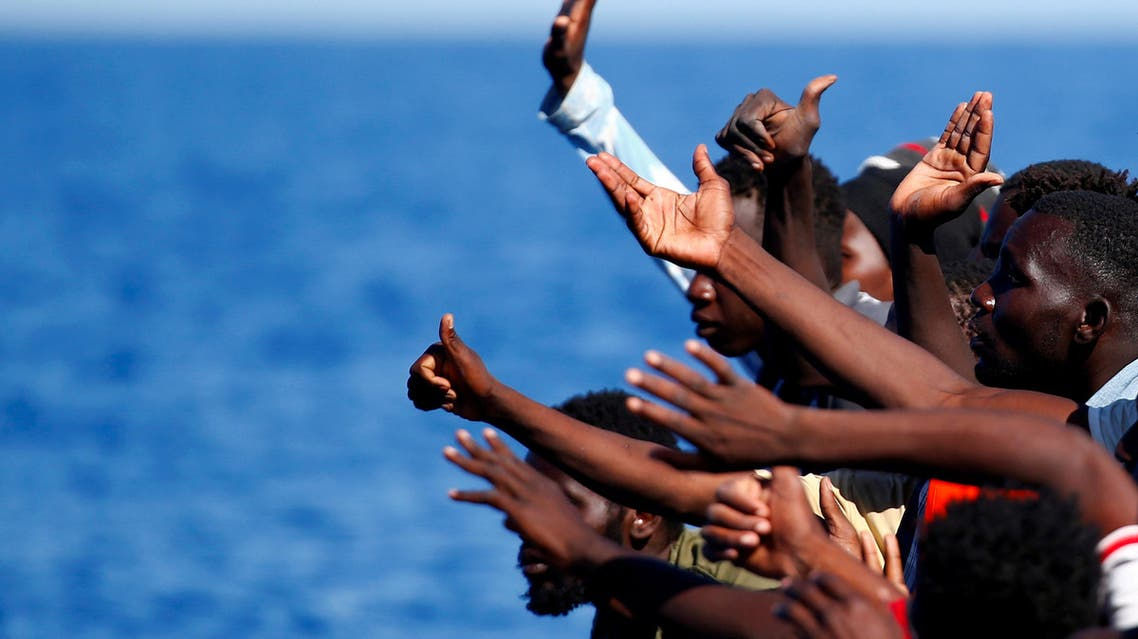FILE PHOTO: Migrants on a rubber boat gesture before they are rescued by the SOS Mediterranee organisation during a search and rescue (SAR) operation with the MV Aquarius rescue ship (not pictured) in the Mediterranean Sea, off the Libyan Coast, September 14, 2017. REUTERS/Tony Gentile/File Photo