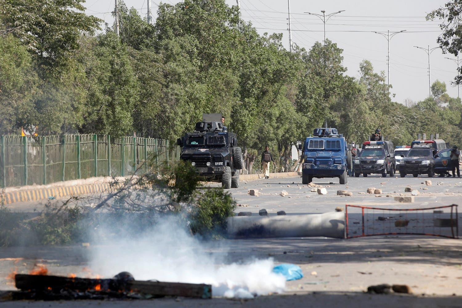 A policeman walks with armoured personnel carriers (APC) as they try to remove hurdles put up by the supporters of the Tehreek-e-Labaik Pakistan along the main road leading to the airport in Karachi. (Reuters)
