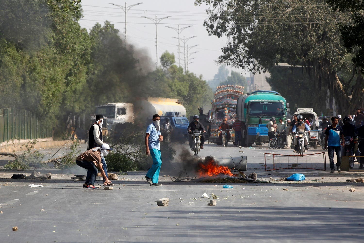 Supporters of the Tehreek-e-Labaik Pakistan place hurdles and block the main road leading to airport in Karachi. (Reuters)