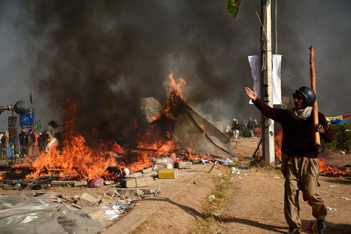 A protester walks near burning tents during clashes with police at Faizabad junction in Islamabad. (Reuters)
